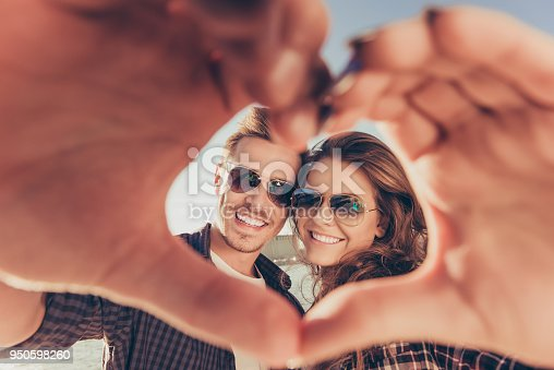 950598260 istock photo Romantic couple in love gesturing a heart with fingers 950598260