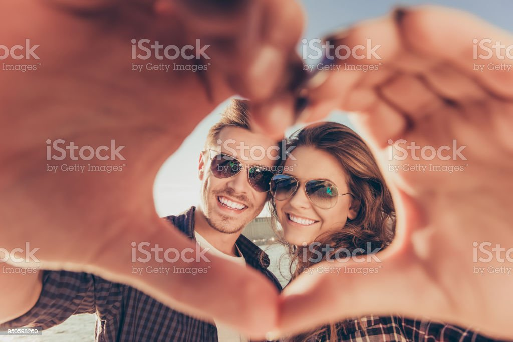 Romantic couple in love gesturing a heart with fingers stock photo