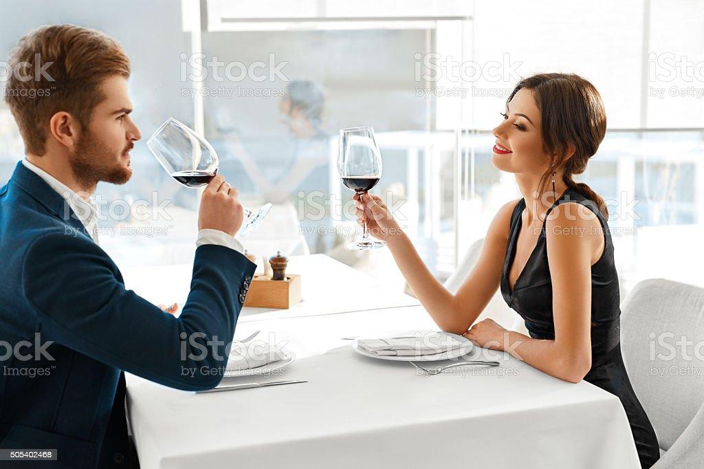 Romantic Couple In Love Having Dinner, Drinking Red Wine In Modern...