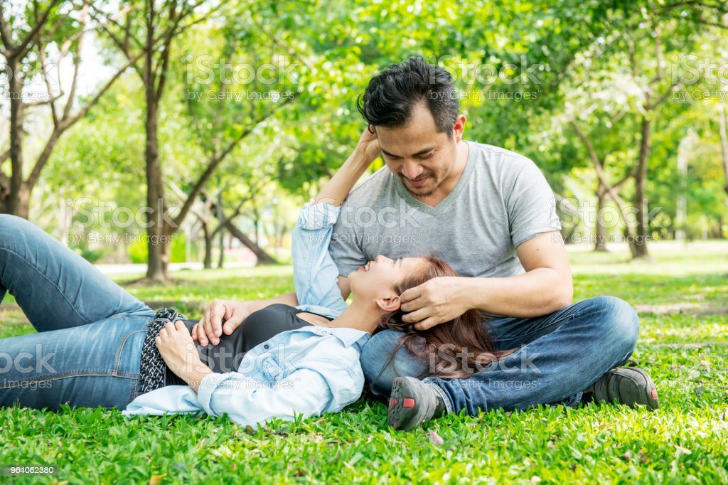 Romantic couple in park. Chinese asian man and woman in park relaxing and loving each other. - Royalty-free Adult Stock Photo