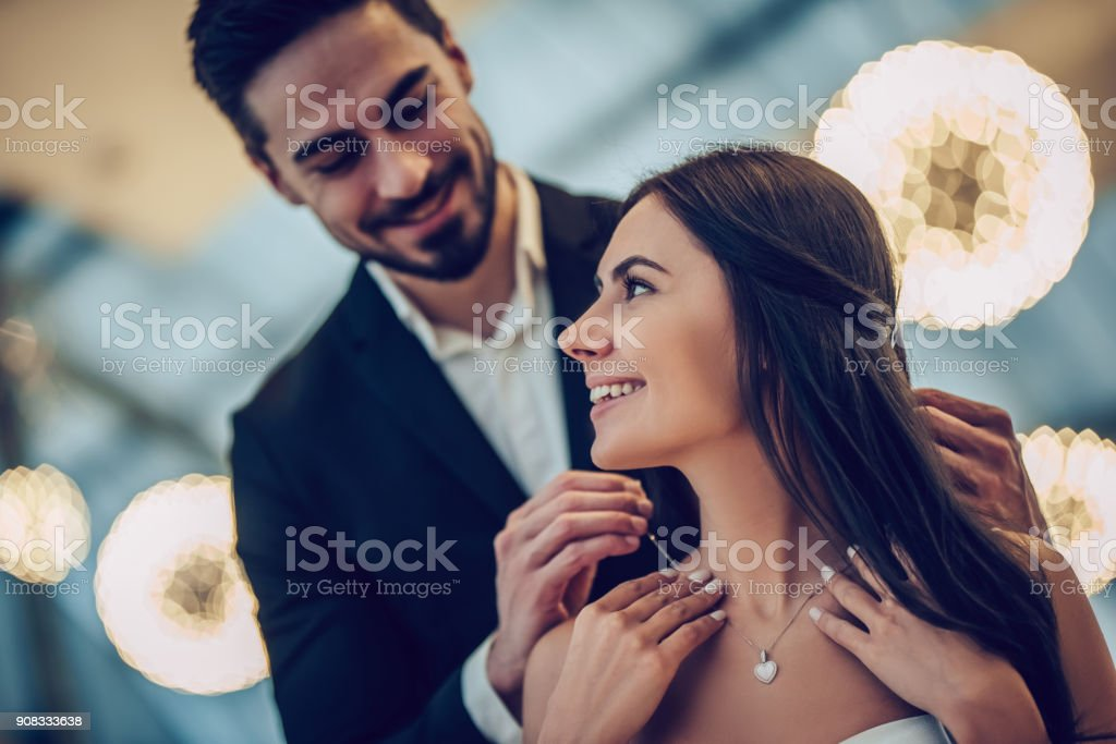 Romantic couple in restaurant Beautiful loving couple is spending time together in modern restaurant. Attractive young woman in dress and handsome man in suit are having romantic dinner. Celebrating Saint Valentine's Day. Adult Stock Photo