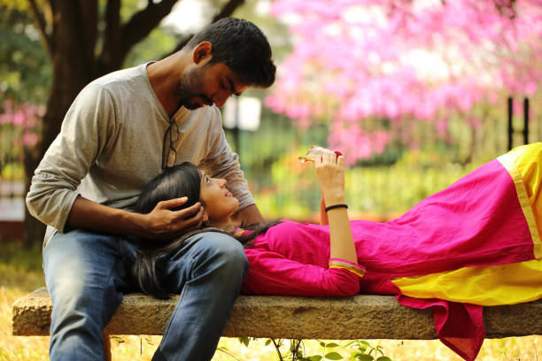Romantic Couple in the Park Beautiful girl lying down on park bench by resting her head on boyfriend's thighs. romance stock pictures, royalty-free photos & images