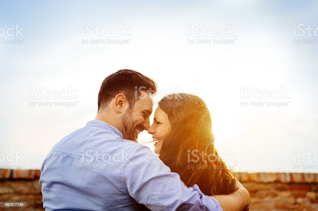 Romantic couple kissing during sunset stock photo