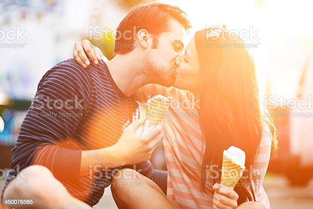 Romantic Couple Kissing While Holding Ice Cream Stock Photo - Download Image Now