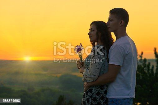 romantic couple look on sun, evening on outdoor, beautiful landscape and bright yellow sky, love tenderness concept, young adult people