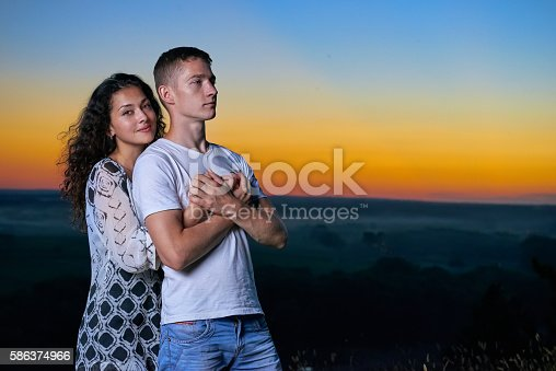romantic couple portrait at sunset on outdoor, beautiful landscape and bright yellow sky, love tenderness concept, young adult people
