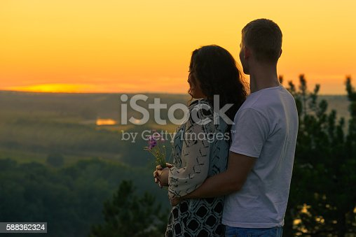 romantic couple look on sunset on country outdoor, beautiful landscape and bright yellow sky, love tenderness concept, young adult people