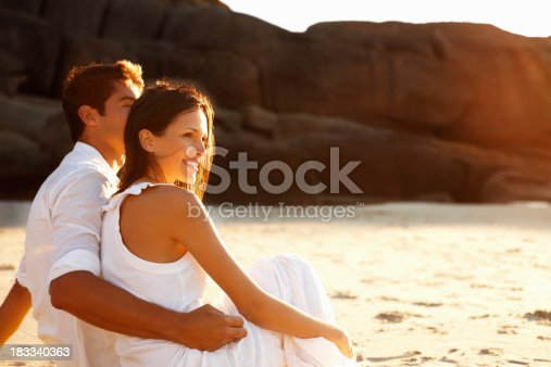 Man and woman looking out to sea at sunset