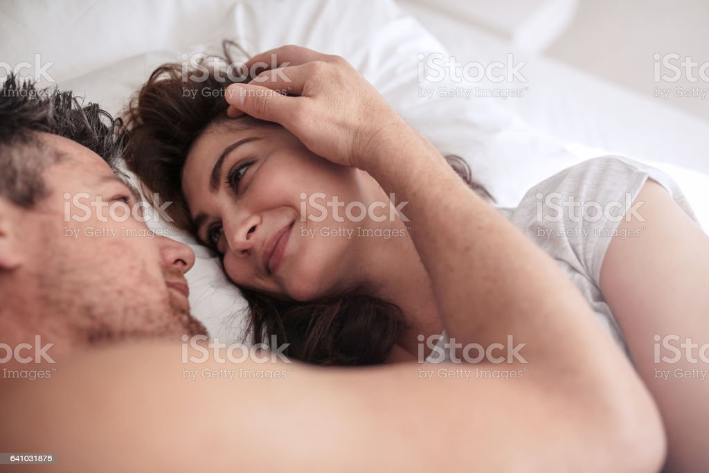Romantic couple lying together on bed stock photo