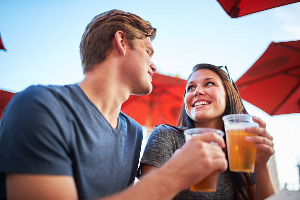 romantic couple making a toast with cups of draft beers stock photo