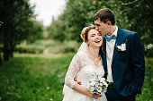 Romantic couple newlyweds, bride and groom stands and holding bouquet of flowers and greens, greenery in the garden. Wedding ceremony on nature.