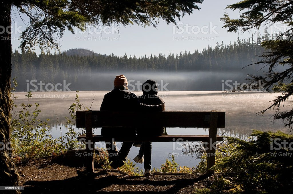 Romantic Couple on Lakeside Bench stock photo