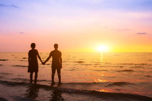 Romantisches Ehepaar am Strand bei Sonnenuntergang, Horizont, Flitterwochen-Urlaub am Meer, Silhouette von zwei Liebhabern, die Hand halten – Foto