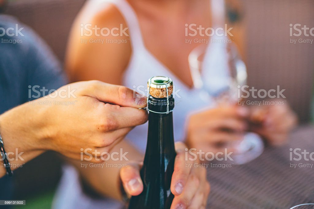 romantic couple opening a wine bottle in an outdoor party stock photo