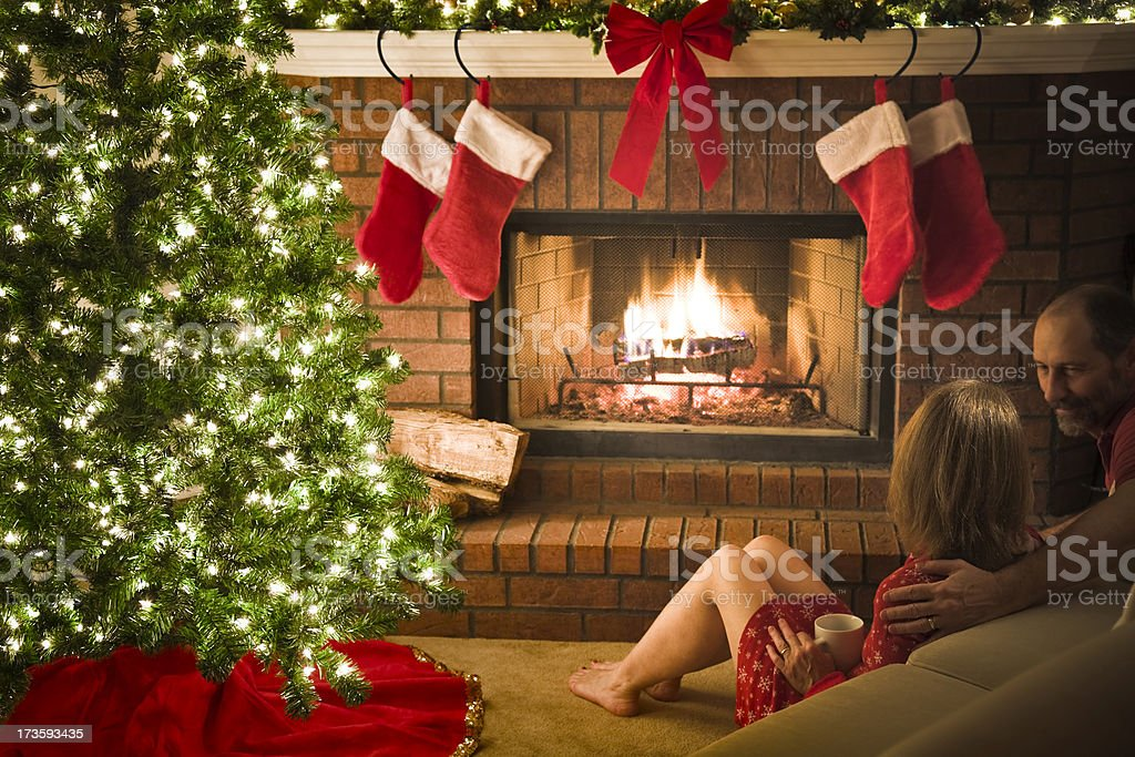 romantic couple relaxing by blazing fireplace and decorated Christmas tree royalty-free stock photo