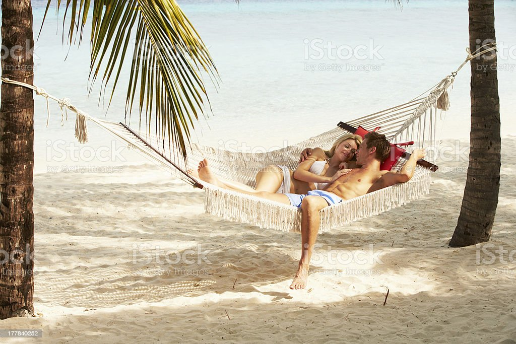 Romantic Couple Relaxing In Beach Hammock stock photo