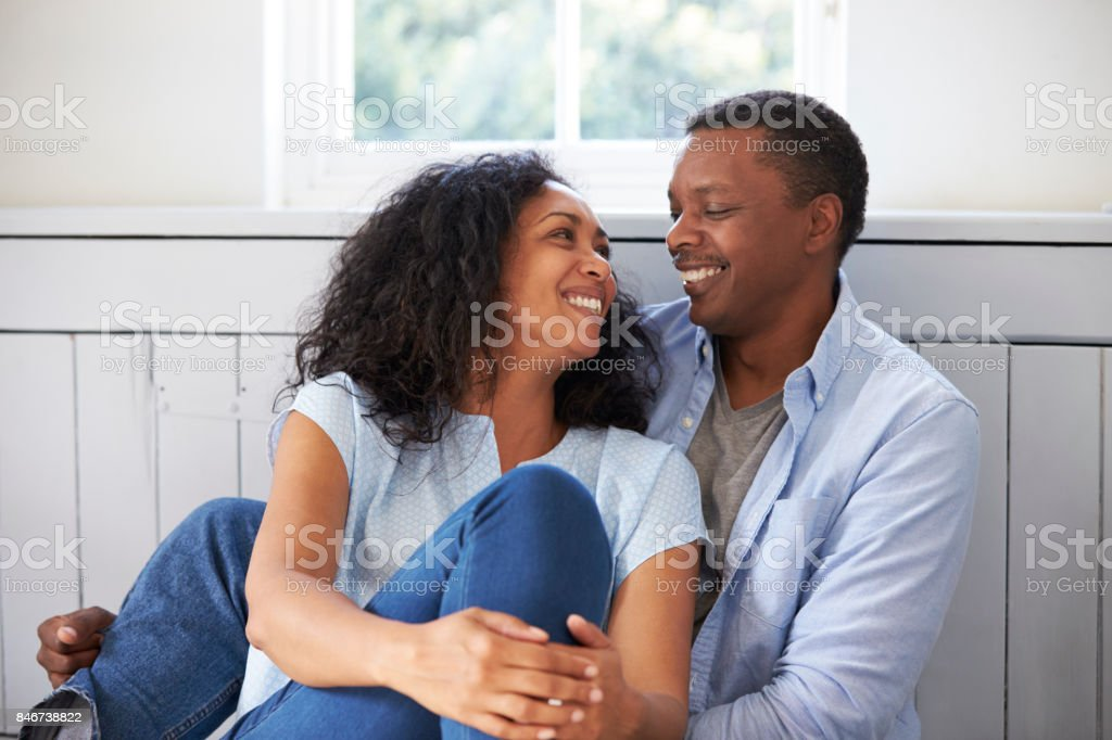 Romantic Couple Relaxing In Chair At Home stock photo