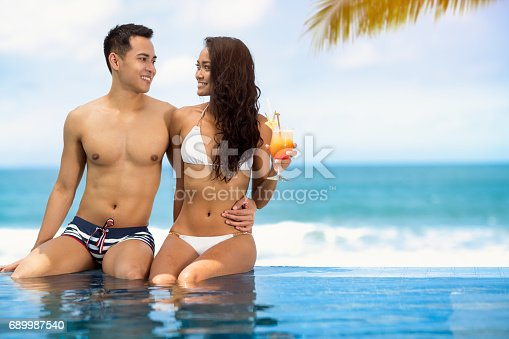 1065243116 istock photo romantic couple relaxing near swimming pool 689987540