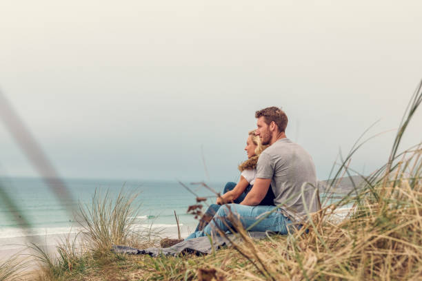 romantic couple sat on sand dunes above fistral beach, newquay, cornwall on an autumn day. - cornwall stock pictures, royalty-free photos & images