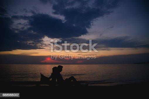 492610640istockphoto Romantic couple sitting on the beach at sunset 688988002