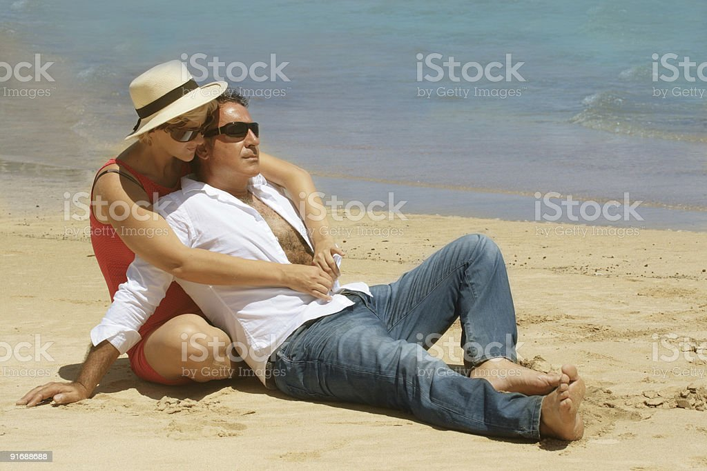 Romantic couple sitting on the beach stock photo