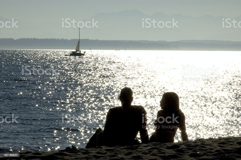 Romantic Couple Sitting on the Beach - Silhouette royalty-free stock photo