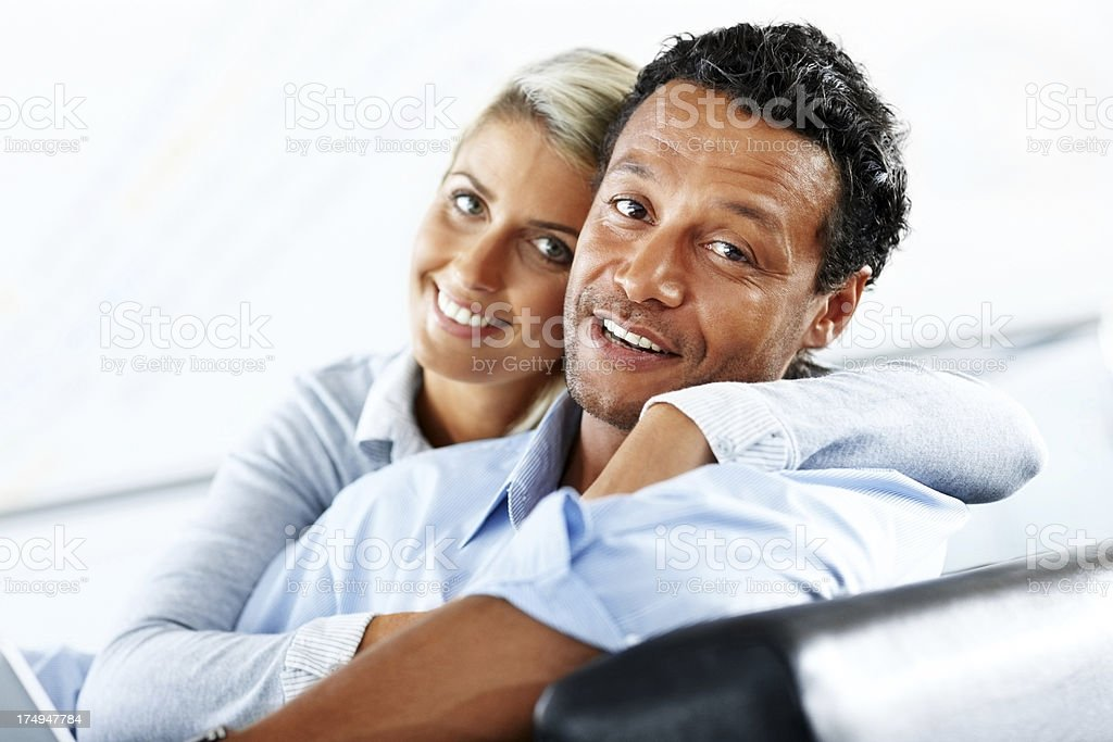 Romantic couple sitting together looking at camera smiling royalty-free stock photo