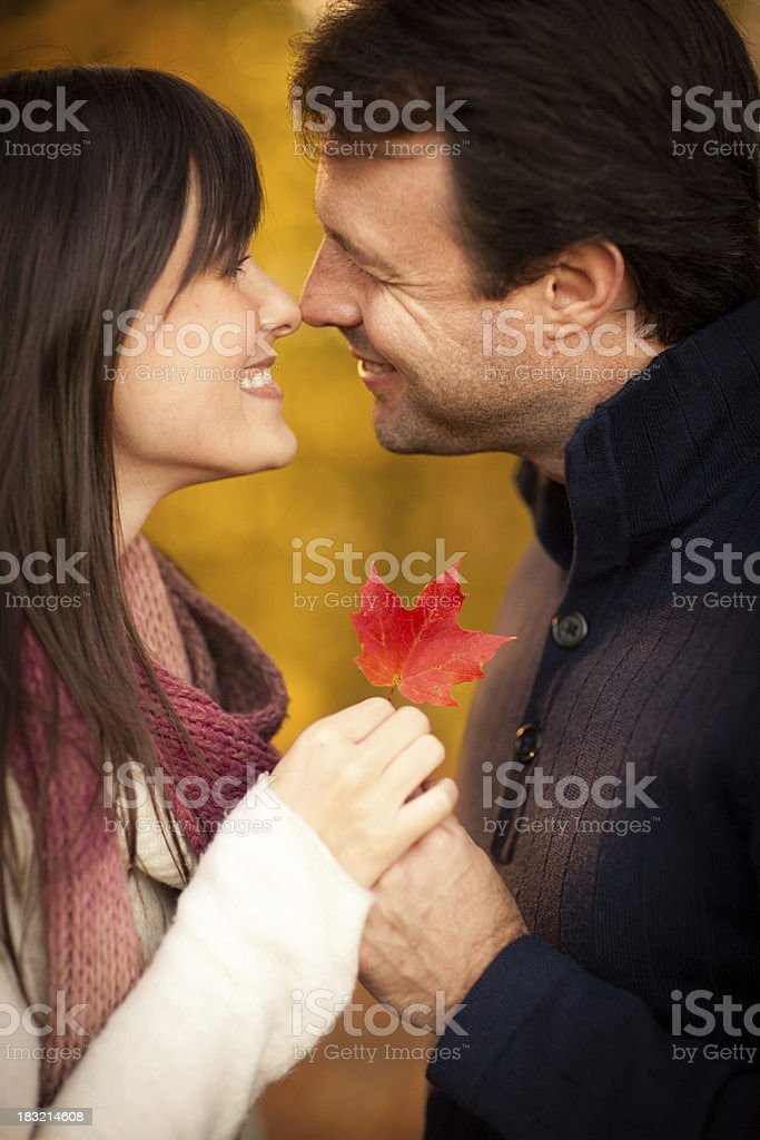 Romantic Couple Smiling While Holding Autumn Leaf Outside During Fall royalty-free stock photo