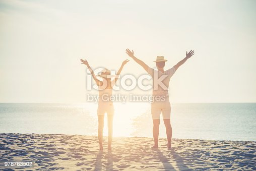istock romantic couple standing hands up happy enjoying sunset at the beach 978763502
