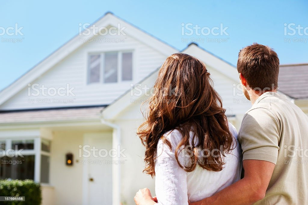 Romantic couple standing in front of their new house stock photo
