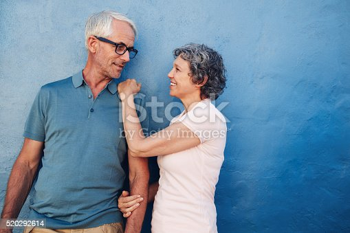 529076288 istock photo Romantic couple standing together against a blue wall 520292614
