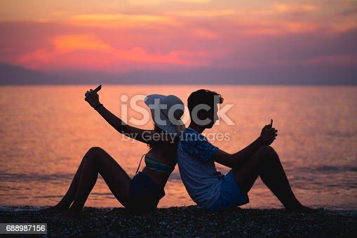 492610640istockphoto Romantic couple taking selfie at sunset 688987156