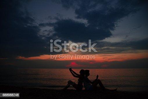 492610640istockphoto Romantic couple taking selfie at sunset 688988248