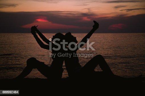 492610640istockphoto Romantic couple taking selfie at sunset 688992464