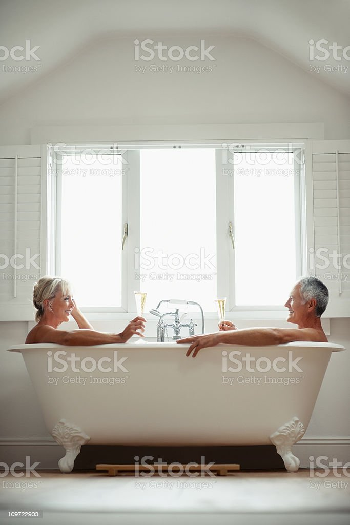 Romantic couple toasting champagne glasses in a bathtub royalty-free stock photo