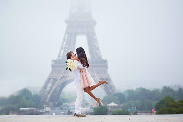 Romantic couple together in Paris Beautiful romantic couple in love with bunch of white roses having fun near the Eiffel tower in Paris on a cloudy and foggy rainy day honeymoon stock pictures, royalty-free photos & images