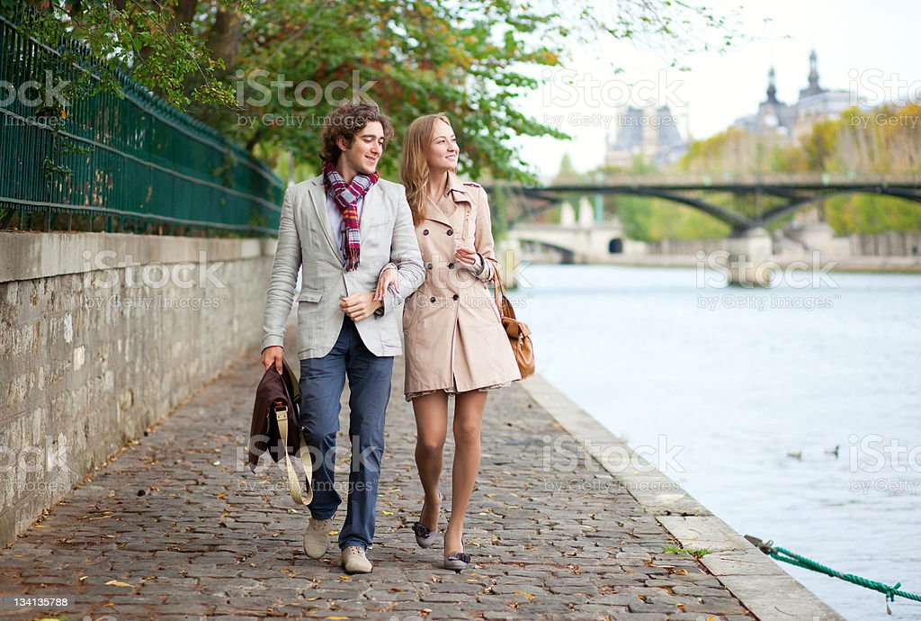 Romantic couple walking on an embankment in Paris royalty-free stock photo