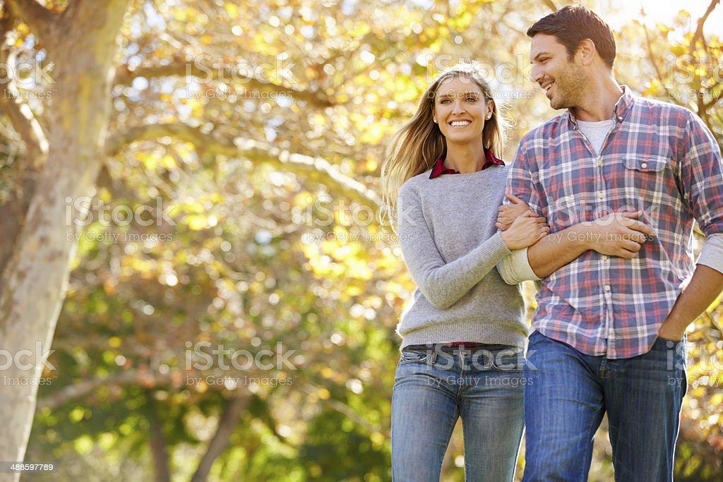 Romantic Couple Walking Through Autumn Woodland Romantic Couple Walking Through Autumn Woodland Linking Arms Smiling 30-39 Years Stock Photo