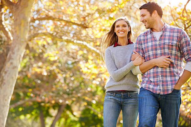 romantica coppia a piedi attraverso il bosco autunnale - forest bathing foto e immagini stock