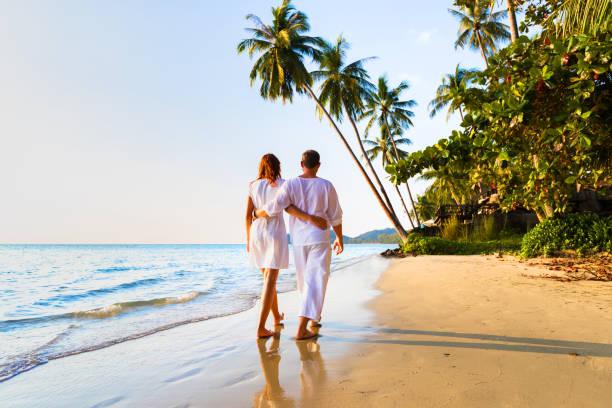 Romantic couple walking together on tropical beach sunny summer picture id868399792?b=1&k=6&m=868399792&s=612x612&w=0&h=bdb8zkc xc2l2rnhrlrxvfjj50dufurakcoiqhtp9t8=