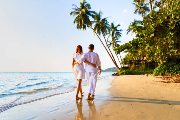 Romantic couple walking together on tropical beach, sunny summer honeymoon stock photo