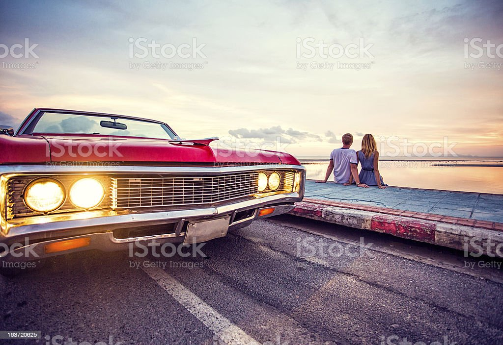 Romantic couple watching sunset with retro car royalty-free stock photo