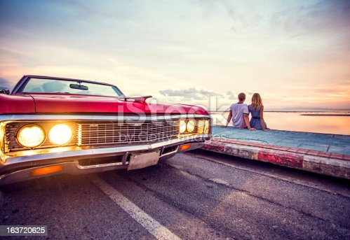 Romantic couple watching sunset with retro car.