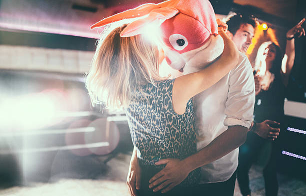 romantic couple, with guy in a bunny head dancing together - mask disguise stock photos and pictures