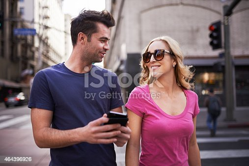 romantic couple with smartphone walking through los angeles during the day