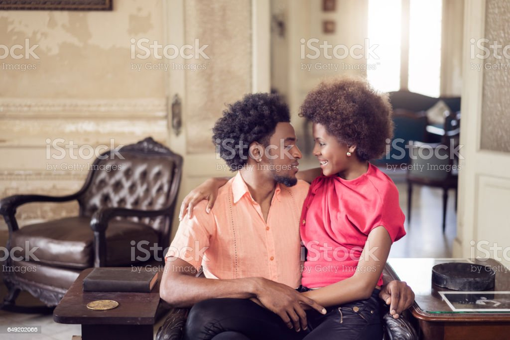 romantic cuban couple looking at each other while sitting on armchair stock photo