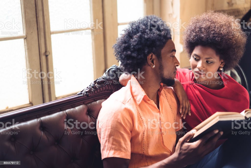 romantic cuban couple reading book together stock photo