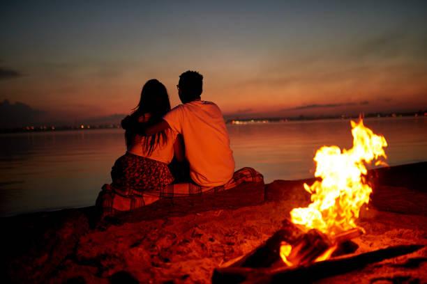 romantic date on beach at night - falò spiaggia foto e immagini stock
