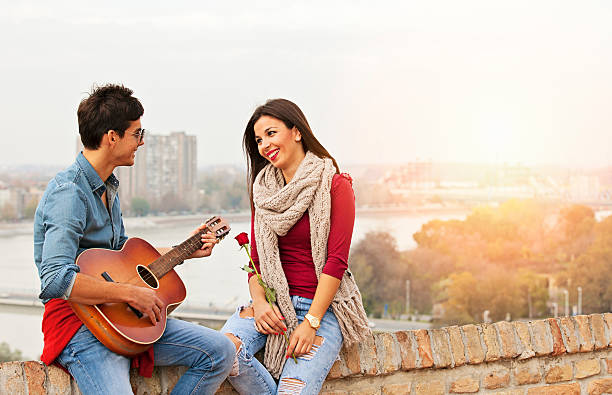 Romantic date outdoors Happy smiling couple on a romantic date, playing guitar serenading stock pictures, royalty-free photos & images
