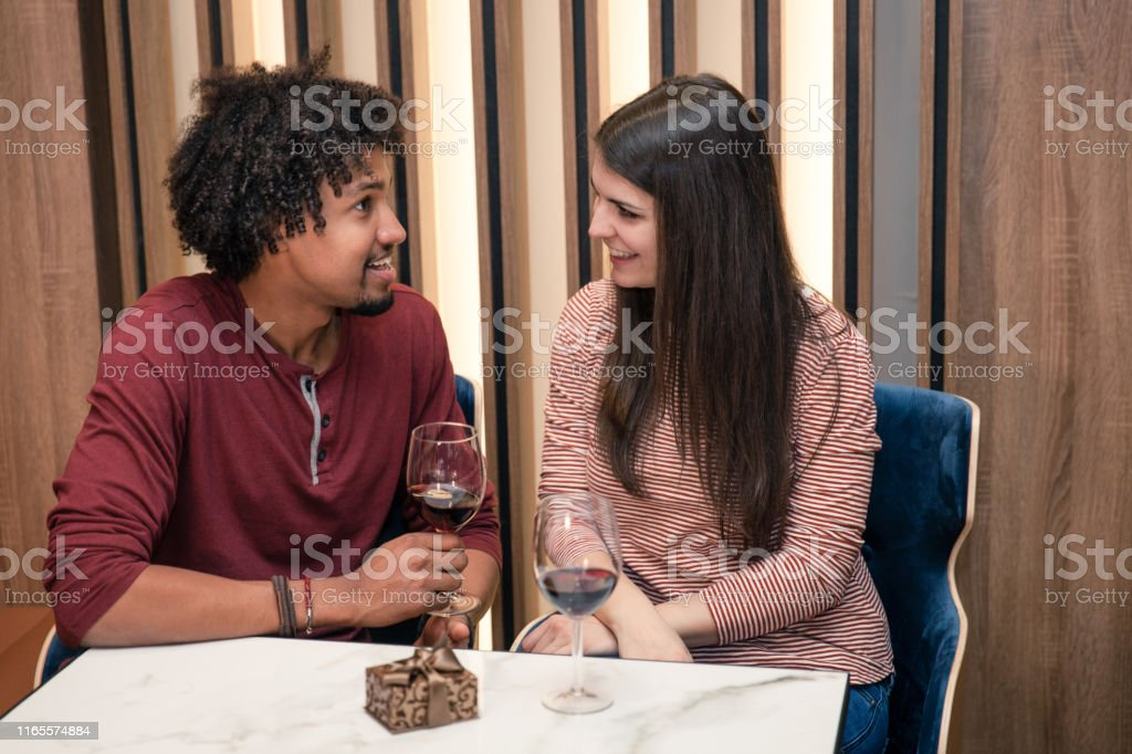 Romantic Date biracial couple in their twenties having red wine together on a date 20-29 Years Stock Photo